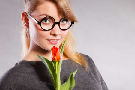 subtlety: Delicacy and subtlety of women. Young adorable woman with spring flower. Portrait of beauty delicate girl in glasses with red beautiful tulip. Stock Photo