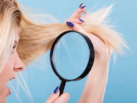 damaged: Haircare and hairstyling, bad effects of bleaching concept. Shocked blonde woman looking at her damaged, split hair ends through magnifying glass.