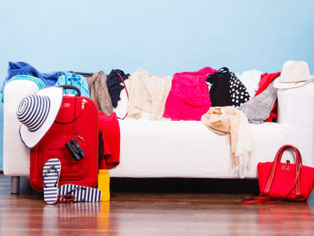 untidy: What to wear, packing for travel concept. Messy colorful clothing lying on white sofa