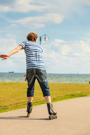roller blade: Holidays, active lifestyle freedom concept. Young fit man on roller skates riding outdoors on sea coast, guy rollerblading on sunny day