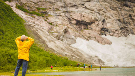 jostedalsbreen: Travel concept. Tourist man looking up at rocky snowy mountains landscape in Norway