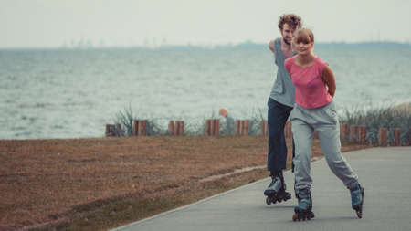 roller blade: Relax leisure love romance dating sport fitness concept. Boy chasing his girlfriend. Couple spending time together skating on rollerskates. Stock Photo