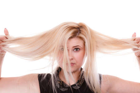 Hair care mistakes, bleaching problems concept. Blonde woman holding her dry, damaged hair.