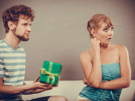 couple on couch: Couple sitting on couch at home. Young man giving offended woman gift box, girl refusing to accept present Stock Photo