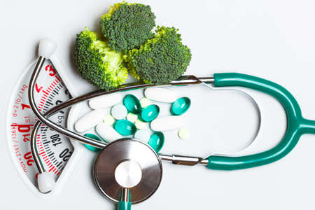 Diet healthy eating weight control and health care concept. Closeup green broccoli stethoscope pills on white scales, choice between