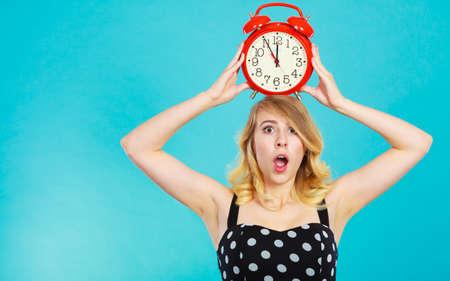 Gestion concept de temps. Blonde fille émotionnelle choqué expression avec une robe parsemée de réveil sur le bleu. Banque d'images - 76098178