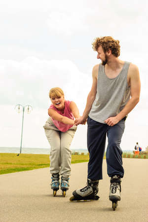 Active holidays, exercises, relationship concept. Young man dressed in sports clothes putting his girlfriend up to do rollerblading while holding her hand on promenade