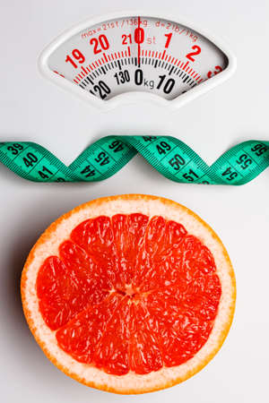 Dieting healthy eating slim down concept. Closeup grapefruit slice with measuring tape on white weight scale Stock Photo