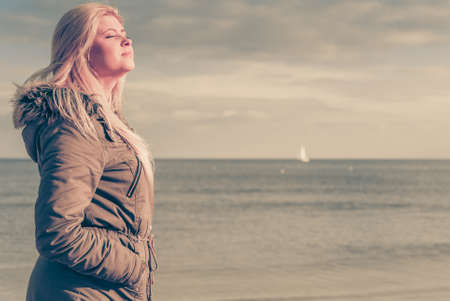 d: Leisure, spending free time outside, healthy walks concept. Woman wearing warm jacket relaxing on beach near sea, cold sunny day