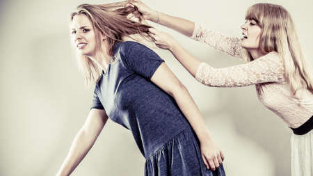 catfight: Aggressive mad women fighting each other pulling hair. Two young girls struggling win catfight. Violence.
