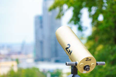 Discovering, science, urban geography, tourist attractions concept. Gold telescope directed toward the city.