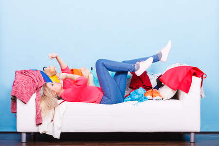 Clothing dilemmas concept. Woman does not know what to wear lying on messy couch with piles of clothes. Stock Photo