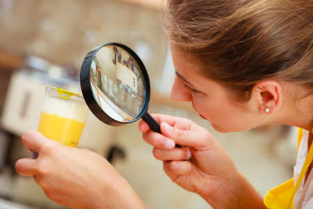 Mature woman female inspecting testing dessert food label with magnifying glass. 스톡 콘텐츠