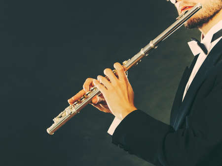 professional flute: Classical music, passion and hobby concept. Elegantly dressed musician man playing on flute wearing black fedora hat. Studio shot on dark grey background