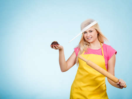 Baking tasty desserts sweets at home concept. Woman holding delicious chocolate cupcake, rolling pin wearing apron and colander on head as hat.