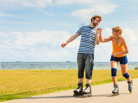 roller blade: Holidays, active people and friendship concept. Young fit couple on roller skates riding outdoors on sea coast, woman and man rollerblading together on the promenade Stock Photo