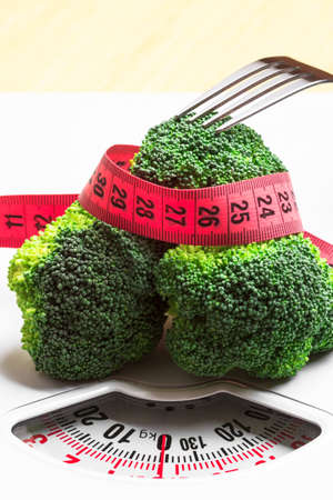 Diet healthy eating weight control concept. Closeup green broccoli measuring tape and fork on white scales