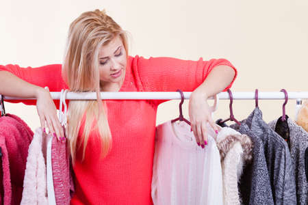 messy clothes: Woman standing in wardrobe with winter clothes, can not decide what to wear. Picking winter clothing concept. Stock Photo