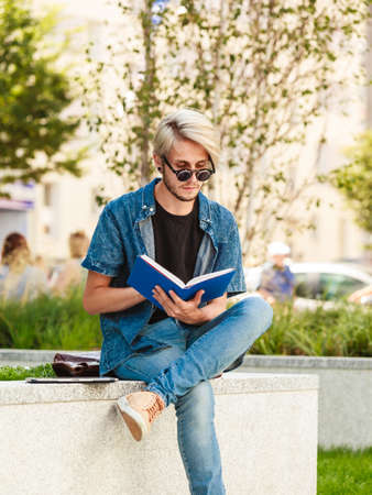 Male fashion, student concept. Guy holding and studying from notebook wearing jeans outfit and eccentric sunglasses sitting on white ledge Stock Photo