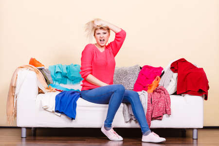 untidy: Clothing dilemmas concept. Shocked woman does not know what to wear sitting on messy couch with piles of clothes.