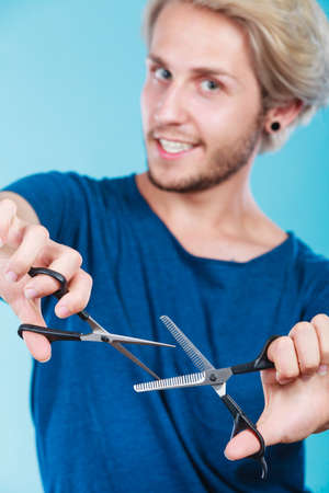 haircutting: Haircut coiffure haircare concept. Passionate male hairdresser holding scissors showing work tools normal and thinning shears