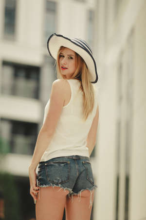 Female fashion, trendy summer clothes concept. Attractive young woman wearing sun hat, white top and denim shorts fashionable summeral style, outdoor shot on sunny day