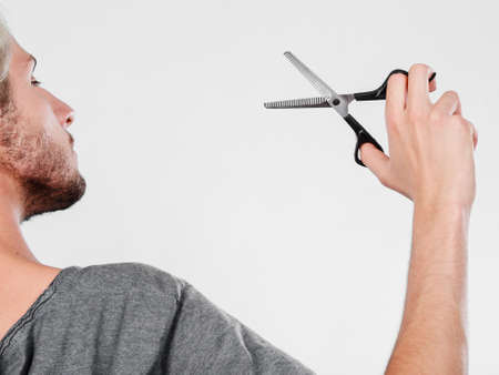 haircutting: Coiffure hairstyle and haircut. Young cool guy holding special shears tool for work of hairdresser.