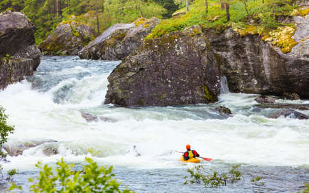 Scandinavian sports concept. People doing extreme white water mountain canoeing in rough river.