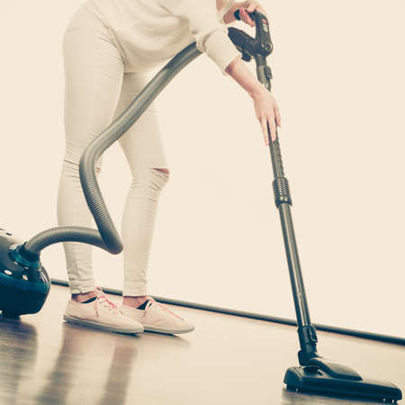Household cleaning tools and devices, housekeeping duties concept. Woman legs and vacuum cleaner Stock Photo
