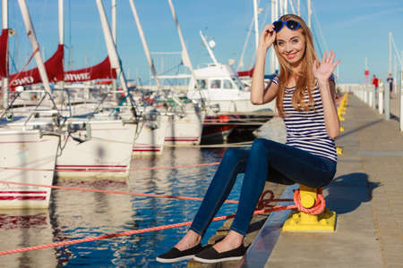 heart shaped: Travel tourism and people concept. Fashion blonde girl with blue heart shaped sunglasses in marina against yachts in port