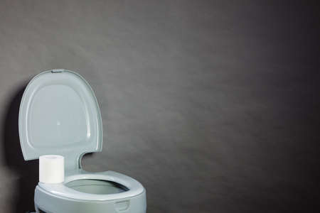Open portable toilet bowl with paper roll, copy space for text
