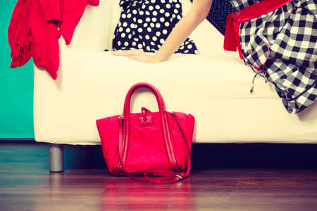 messy clothes: Woman wearing checked dress relaxing on sofa after shopping, red bag next to couch, clothes all over place.