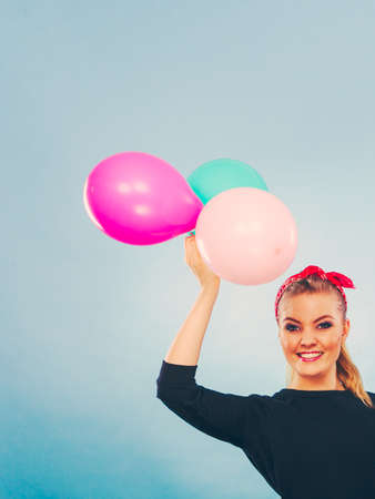 Joy fun and freedom concept. Blonde smiling woman with colorful latex balloons flying balls. Retro fashion styled girl portrait. Stock Photo