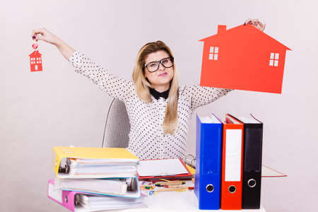 property management: Happy business woman sitting working at desk full off documents in binders, she holding big red house made of paper, real estate concept.