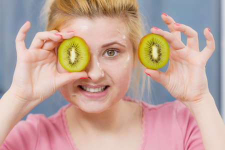 bathroom mirror: Facial skin and body care, vitamins good complexion treatment at home concept. Young woman having gel peel off mask on her face holding kiwi fruit.