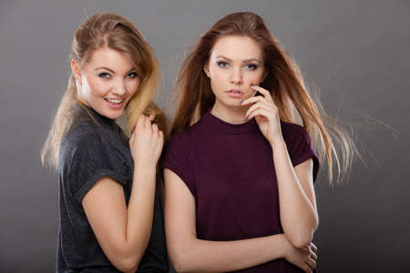 Family relationships, friendship concept. Two beautiful women sisters, blonde and brunette with windblown hair posing charmingly. Studio shot on dark grey background Stock Photo