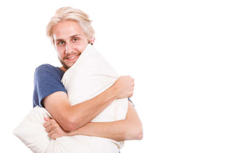 nightwear: Sleeping well concept. Happy young man rested after good night sleep playing with pillows, smiling having fun Stock Photo