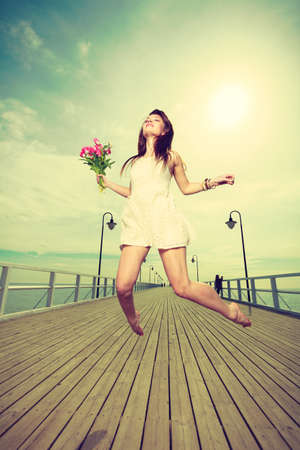Happiness, romance, success concept. Woman wearing short white dress jumping on pier holding bouquet of flowers. Stock Photo