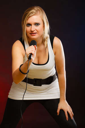 Karaoke, music, singer concept. Portrait of blonde woman singing to microphone, young star performing having fun, studio shot.
