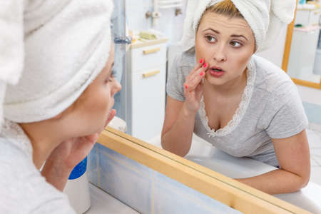 Worried shocked woman looking at her reflection in mirror thinking about her complexes having serious face expression, analyzing face skin complexion.