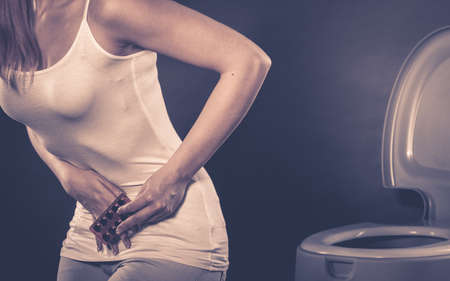 closet: Bellyache, constipation or food poisoning. Woman suffering from strong abdominal pain, holding medical tablets activated carbon in hand, toilet in the background Stock Photo