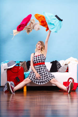 closet: Cleaning in the closet, packing for travel, fashion, happiness concept. Woman sitting on sofa throwing up lot of clothes. Clothing flying all over the place Stock Photo