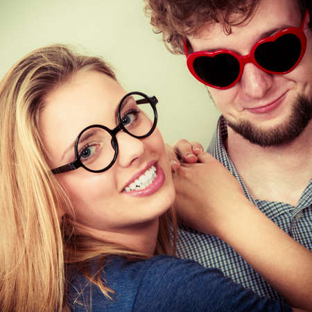 heart shaped: Happy young couple in heart shaped glasses. Smiling friends woman and man in studio.