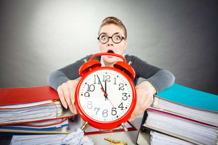 Paper work against time. Young expressive woman in office with big red clock. Unhappy businesswoman so far to ending her work. Stock Photo