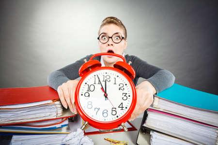 Travail de papier contre le temps. Jeune femme expressive au bureau avec une grosse horloge rouge. Femme d'affaires malheureuse jusqu'à présent pour mettre fin à son travail.