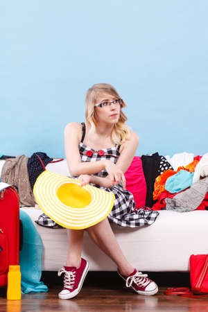 messy clothes: Packing problems, necessary things during the trip concept. Woman sitting on sofa holding sun hat, getting ready for vacation, choosing clothes to pack into suitcase