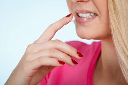 Diet, sweets temptation, delicious food concept. Woman licking whipped cream from finger or applying lip balm to dry lips, presenting her red nails