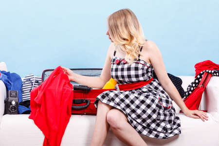 Packing problems, necessary things during the trip concept. Woman sitting on sofa, getting ready for vacation, choosing clothes to pack into suitcase