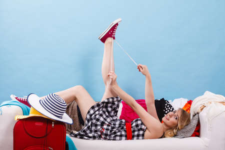 Traveling, waiting for adventure concept. Woman relaxing lying on sofa after packing clothes into her red suitcase. Indoor shot Stock Photo
