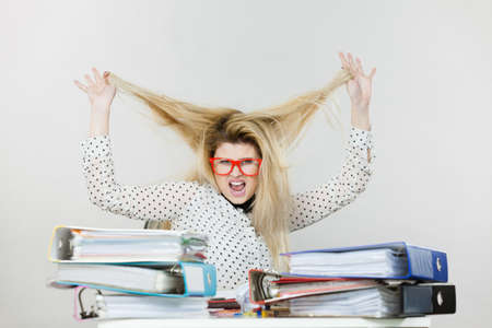 Happy business woman feeling energetic sitting working at desk full off documents in binders playing with her hair.